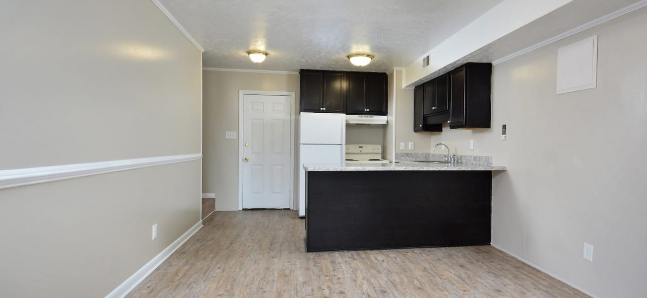kitchen with stylish cabinets, and easy access to the unfurnished space for the living room